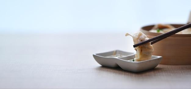 나무 테이블에 간장 소스와 함께 원래 일본 만두 교자. 공간을 복사하십시오.
