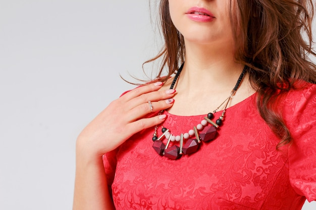 Original necklace on young woman in red elegant dress