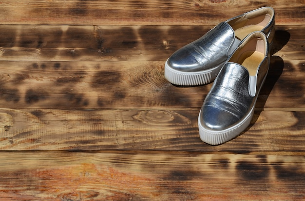 Original shiny shoes in disco style lie on a vintage wooden surface made from fried brown boards.