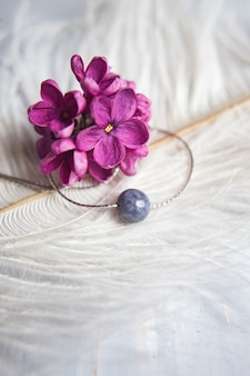 Original silver jewelry necklace made of natural stone with purple violet lilac flowers on white ostrich feather. gift concept. silver accessories. mock up space for text.
