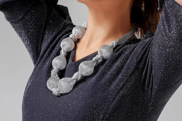 Original silvery large necklace on young woman in shiny blue eve