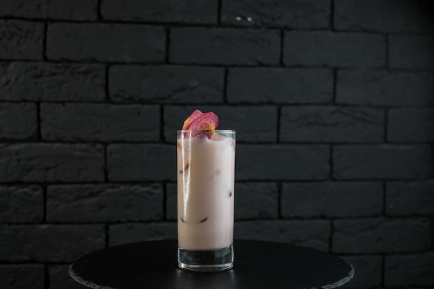 Original sweet white milkshake with strawberry juice with ice cubes tonic and vodka on a black table in the bar. alcoholic drinks