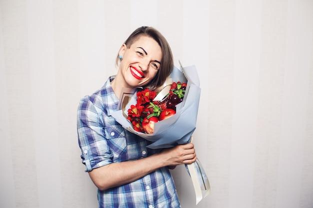 Оригинальный необычный съедобный букет фруктов в руках девушки на светлом фоне