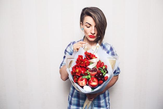 Оригинальный необычный съедобный букет из фруктов в руках девушки на светлом фоне.