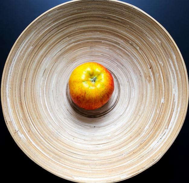 Оригинальная деревянная тарелка со сплошными линиями и одно яблоко на черном столе. органический, натуральный материал чаши с вечными линиями. экологичные фрукты фото. светло-бежевый минимализм плоской планировки.