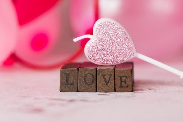 木の杖の愛のタイトルの近くの心の形の装飾のろうそく