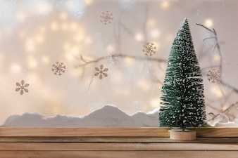 Ornament fir tree on wood table near bank of snow, plant twig, snowflakes and fairy lights