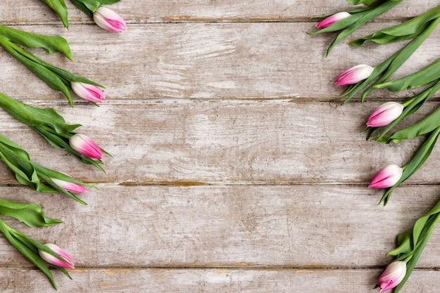 Орнамент из розовых тюльпанов. весенний фон. букет цветов на деревянном фоне с copyspace. свадьба, подарок, день рождения, 8 марта, концепция поздравительной открытки ко дню матери