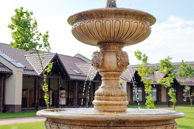 Декоративный фонтан со львиными головами на пешеходной улице в небольшом европейском городе