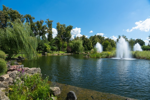 Ornamental fountains in a lake in a scenic landscaped park with rockery and woodland trees under a blue cloudy sky