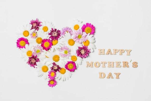 幸せな母の日のタイトルの近くの明るい花の装飾的な心