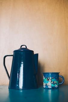 Ornamental porcelain teapot and mug against wooden backdrop