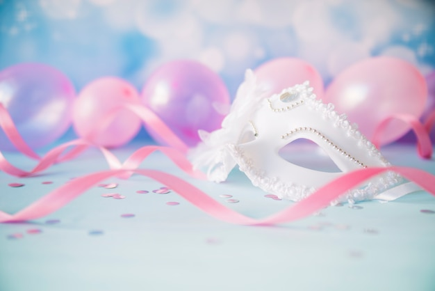 Ornamental white mask in pink streamers
