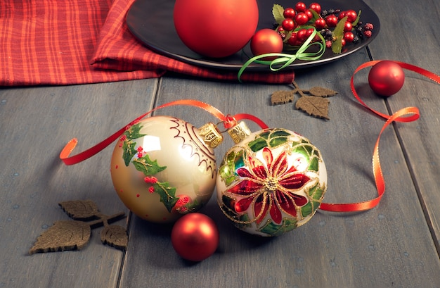 Ornate christmas baubles with christmas star motive tied with ribbon and red napkin on wood