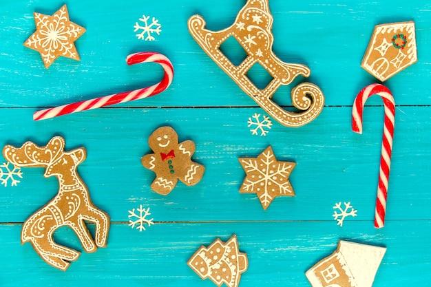 青い木製の背景に華やかなジンジャーブレッドクッキーと雪片。