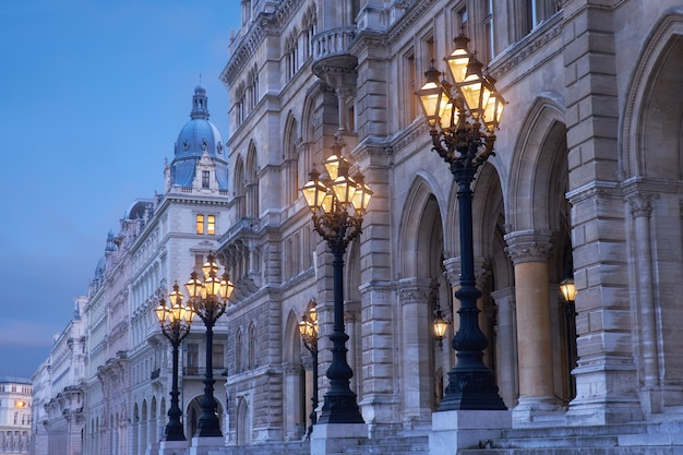 Ornate historical lamp posts outside rathaus vienna, or vienna town hall in the evening