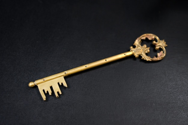 Изысканный старинный латунный ключ на черном с избирательным акцентом на зубы, уложенные по диагонали, с копировальным пространством для магических концепций