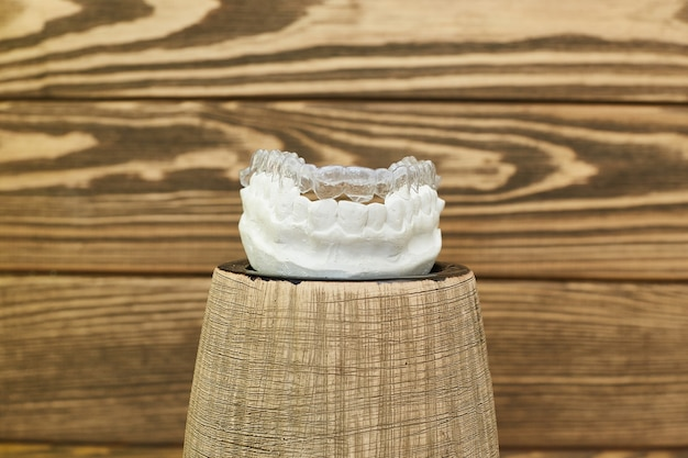 素朴な背景の歯科矯正歯科テーマ。歯科矯正歯科治療のための透明な目に見えないトレイまたはブレース。