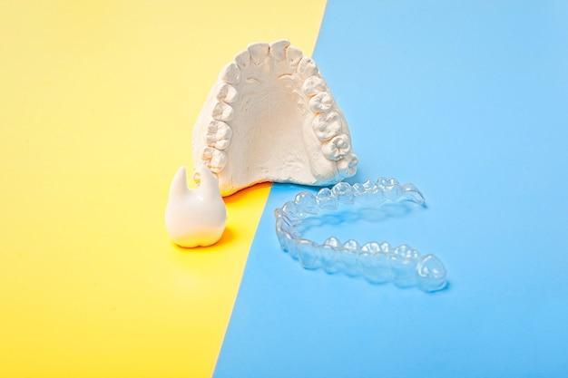 파란색과 노란색 배경에 교정 치과 테마. 투명한 보이지 않는 치과 정렬 장치 또는 교정 치과 치료에 적용 가능한 교정기