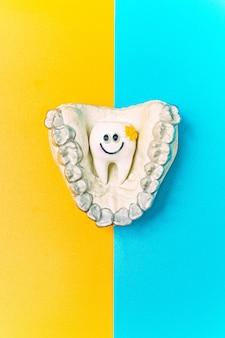 파란색과 노란색 표면에 치열 교정 치과 테마. 투명한 보이지 않는 치과 정렬 기 또는 교정 치과 치료에 적용 할 수있는 교정기