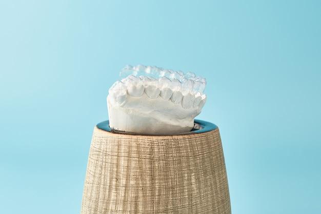 青い背景の歯科矯正歯科テーマ透明な目に見えない歯科用アライナーまたはブレースアプリキャブ