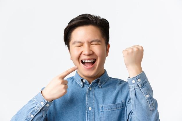 치열 교정 및 구강학 개념입니다. 흥분하고 행복한 아시아 남성이 새 치아 교정기에 기뻐하며 입을 가리키며 웃고 주먹을 쥔 채 흰색 배경 위에 승리하는 모습을 클로즈업