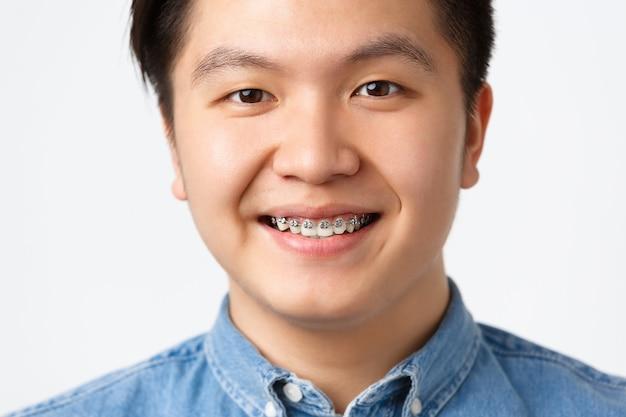 치열 교정 및 구강학 개념입니다. 웃고 있는 행복한 아시아 남성의 헤드샷, 치과 교정기를 보여주고, 진료소를 추천하고, 좋은 결과에 만족하고, 흰색 배경을 기쁘게 생각합니다.