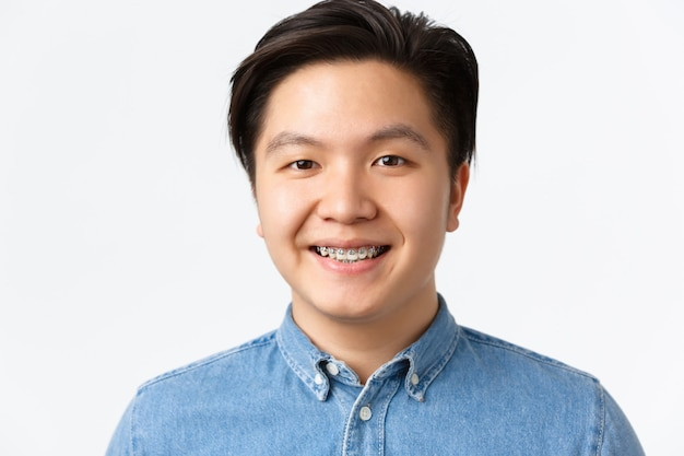 치열 교정, 치과 치료 및 구강학 개념입니다. 치아 교정기를 가진 잘생긴 아시아 남자의 클로즈업 초상화, 기쁘게 웃고, 희망적이고 행복해 보이고, 흰색 배경에 서 있습니다.