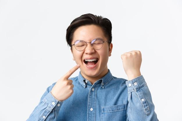 Ortodonzia e concetto di stomatologia. primo piano dell'uomo asiatico felice soddisfatto che indica i suoi apparecchi dentali e sorride ampiamente, pompa a pugno, gioia, fissaggio dei denti, sfondo bianco in piedi.