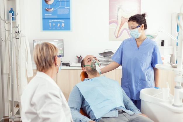 歯科矯正医の助手が、口腔病学の予約中に歯の痛みを分析している患者に酸素マスクを装着します