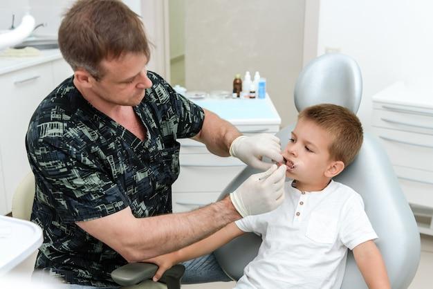 교정 의사는 클리닉에서 아이의 치아를 확인합니다