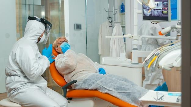 保護カバーオールの歯科矯正医は、口腔病学のオフィスでcovid-19の間に歯痛の患者に話します。保護服を着たコロナウイルスの発生における新しい通常の歯科医の訪問の概念と