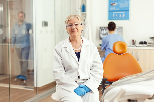 歯科矯正医の先輩が椅子に座って前を見て、患者が歯の手術後に口腔病学治療を開始するのを待っている