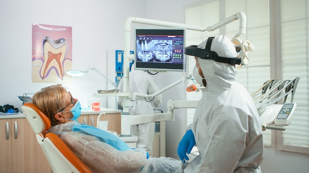 Orthodontist in special equipment pointing on digital x-ray explaining dental treatment during global pandemic. medical team talking with woman wearing face shield, protection suit, mask and gloves