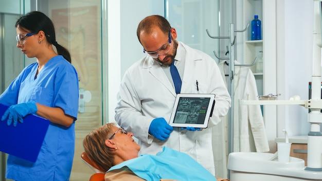 Ортодонт с помощью планшета объясняет стоматологический рентген пациенту, сидящему на стоматологическом кресле в стоматологическом кабинете. стоматолог показывает пожилой женщине рентгенографию с помощью цифрового устройства, работающего в современной клинике.