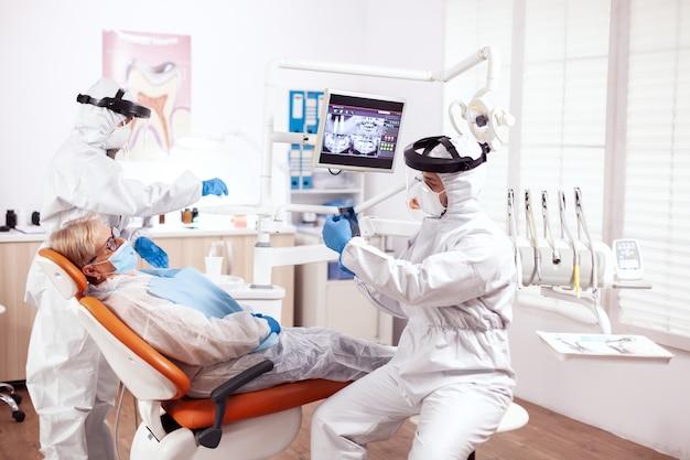 制服を着た矯正歯科医がシニア患者に相談するコロナウイルスに感染しました。歯科医院での診察中に防護服を着た年配の女性。