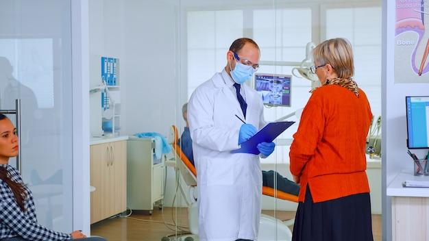 마스크를 쓴 교정 의사는 구강 진료소 대기실에 서서 클립보드에 메모를 하고 있는 노인 여성과 이야기하고 있습니다. 현대 붐비는 사무실에서 컴퓨터 약속에 타이핑하는 간호사