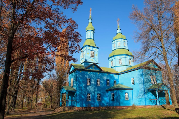 Orthodox blue wooden church in the autumn park in pereyaslav khm