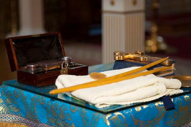Православная церковь. свечи, крест, значок, молитвенник, библия на столе. предметы для церемонии в храме. подготовка к крещению новорожденного в святой воде. таинство крещения