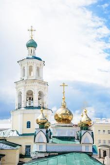 Православная церковь с золотыми и синими куполами и крестами с колокольней на фоне голубого неба
