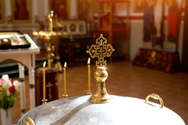 Orthodox cross in the sun on the lid of the bowl for the rite of infant baptism