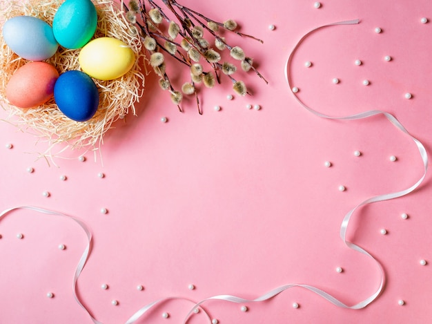 Orthodox easter concept. colorful eggs and pussy willow branches on pink background with empty chalkboard.
