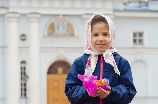Православная пасха. девушка с крашеными пасхальными яйцами над церковью