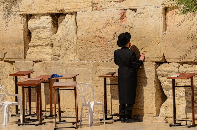 Orthodox jewish man praying at the western wall in jerusalem, israel