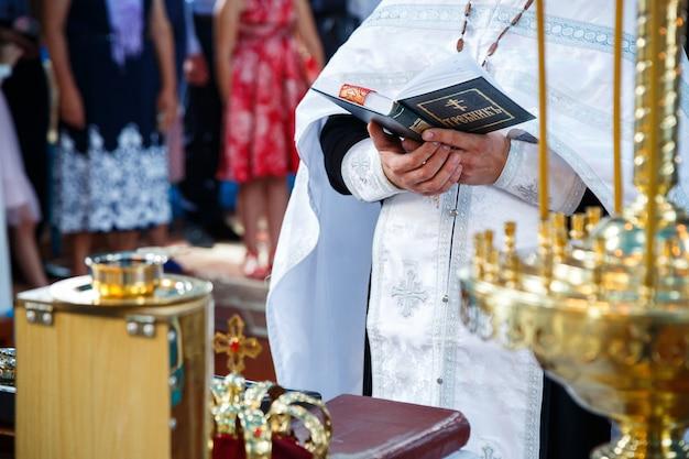 Православная религия. руки священника на библии.