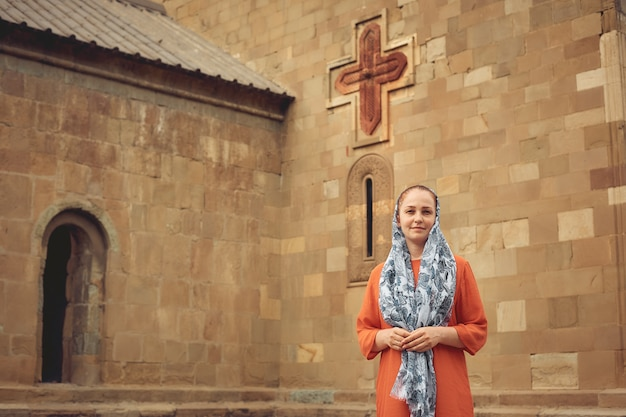 Orthodox woman by an ancient christian church