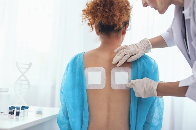 정형 솔루션. 전문 정형 외과 의사가 통증 완화 고약을 적용하여 신중하게 검사하는 등 위쪽을 가진 젊은 아가씨