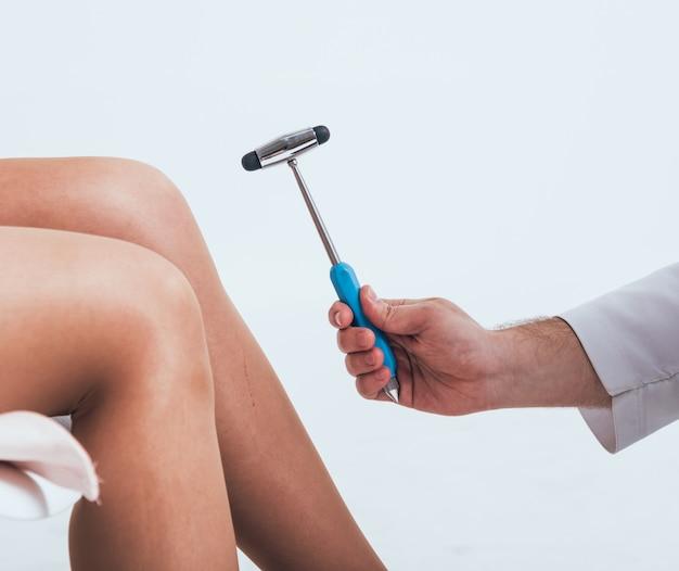 Хирург-ортопед осматривает коленный рефлекс. доктор