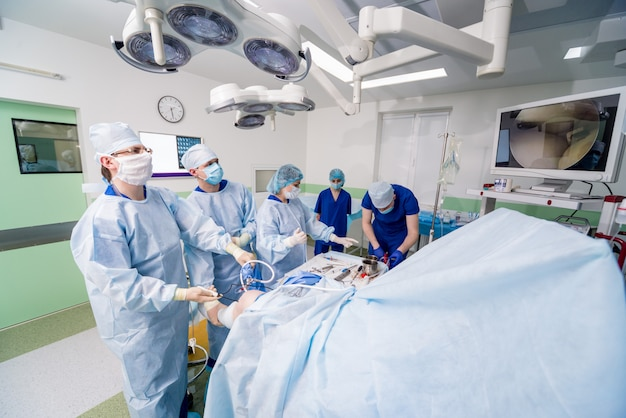 Orthopedic surgeons in teamwork in the operating room with modern arthroscopic tools.