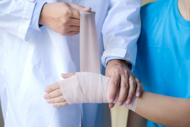 Orthopedist applying wrist elastic wrap on male patient hand joint dislocation